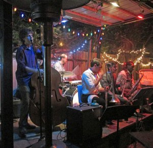 The Roamin' Jasmine performing at Bacchanal. Taylor is on bass (left).